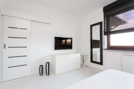 closet door: Vibrant cottage - white commode and black tv in bedroom