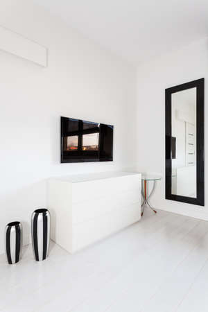 Vibrant cottage - white commode and black tv photo