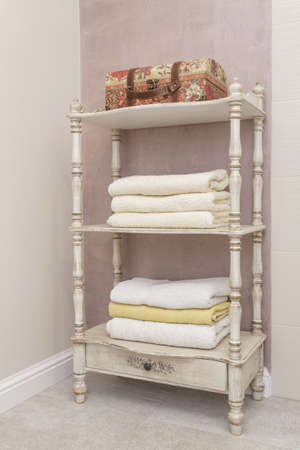 Tuscany - wooden bright shelf with towels photo