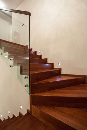 Travertine house- Closeup of wooden, glass stairs in modern interior photo