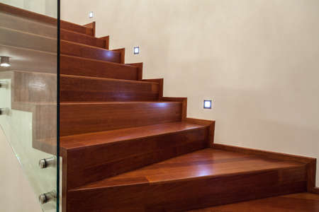 Travertine house- Horizontal view of brown, wooden stairs in luxury interior photo