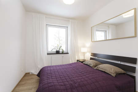 Cosy flat - violet bed in white bedroom Stock Photo - 19131300