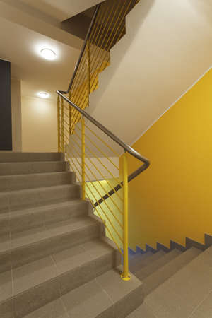 Yellow staircase with metal banister photo