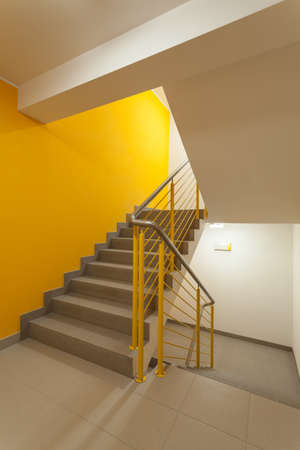 Staircase with yellow walls and metal banister photo