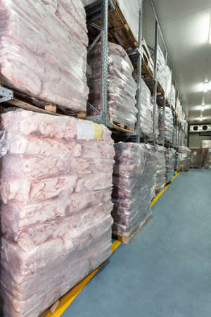Frozen meat in a huge warehouse, vertical photo