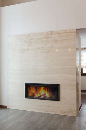 Grand design - Burning fireplace in marble wall photo