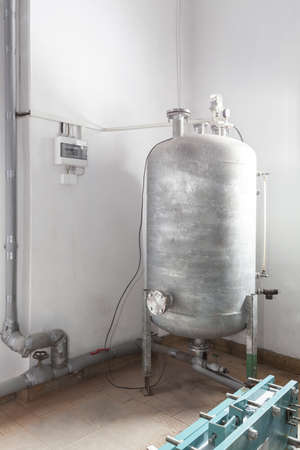 condensing: Silver expansion tank inside of cold store Stock Photo