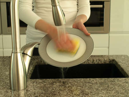 dish washing: Washing plate under running water after meal