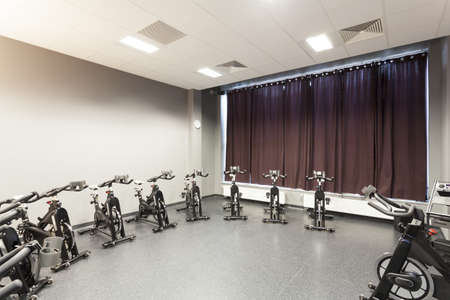 Stationary bicycles standing in a fitness gym photo