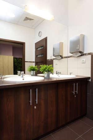 Wash basin in wooden counter in public bathroom photo