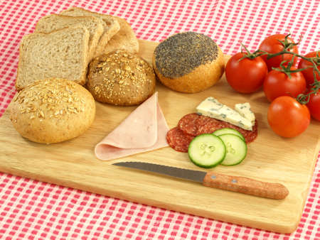 picnic tablecloth: Bread, meat and vegetables for picnic on cutting board  Stock Photo