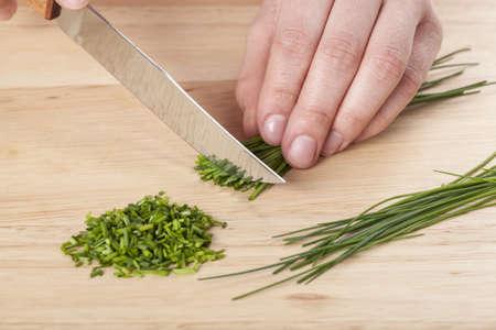 cebollin: Picar la cebolleta verde en la tabla de cortar