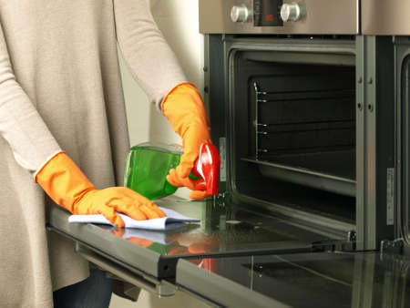 clean room: Polishing the oven with rubber and special spray Stock Photo