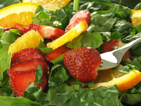 mixed fruits: Closeup of salad with strawberry, orange and spinach