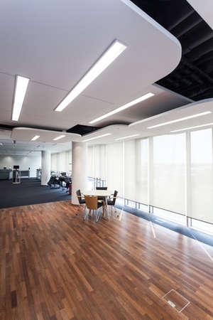 Современный офис с дизайном освещения и деревянный пол.