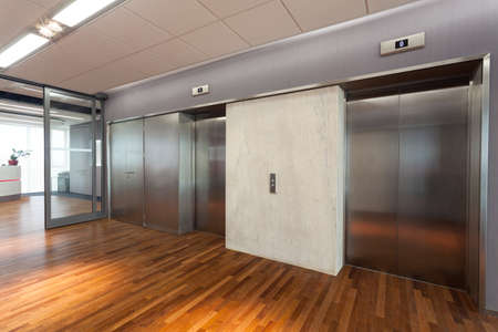 two companies: Office interior, hall with two elevators Stock Photo