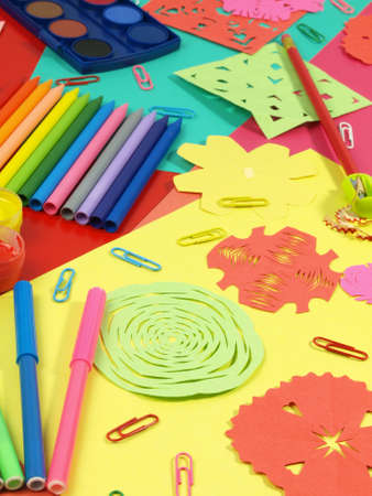 Colorful papers, crayons, paints in a children photo
