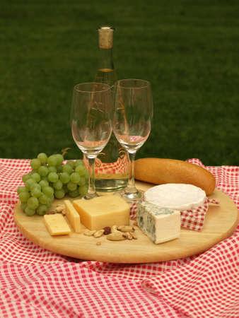 tabla de quesos: Picnic en una hierba con tabla de quesos, de cerca Foto de archivo