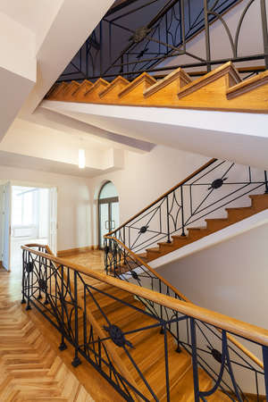 Wooden elegant stairs with a metal ornalental banister photo