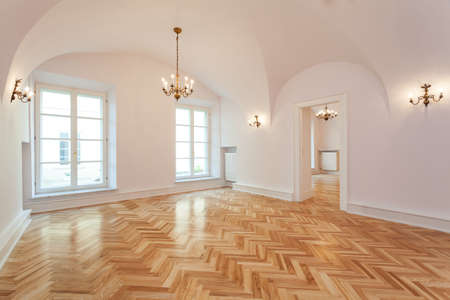 Interior of an empty palace with a wooden floor and chandelier.