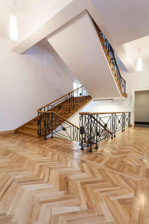 Staircase in elegant style with wooden steps and metal banister photo