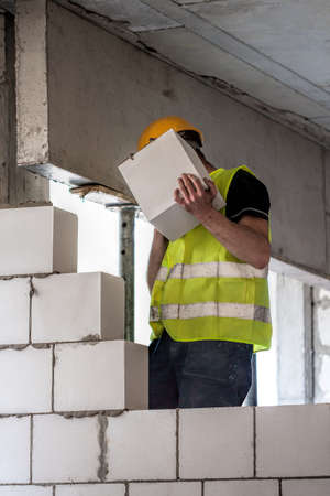 bricklayer: Bricklayer holding piece of a concrete block