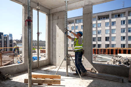 Worker on a building site adjusting supports Stock Photo