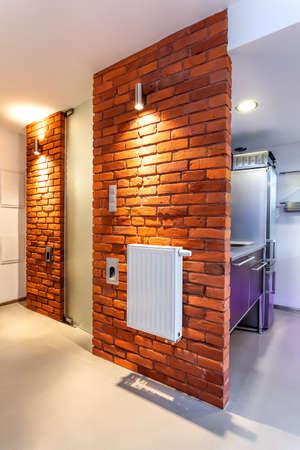 Bakstenen muur met witte kachel in een gang