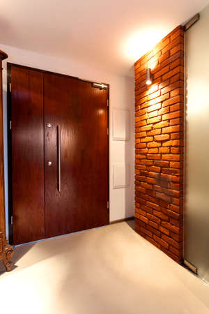 Huge wooden door in a house with brick wall photo