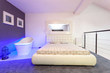 White and purple bedroom with modern bathtub Stock Photo - 20077438