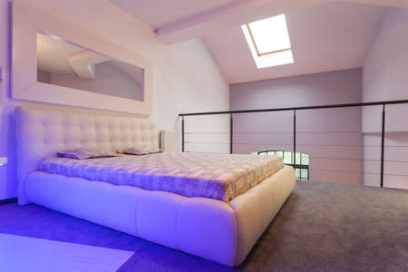 Huge white bed standing on the balcony, loft photo