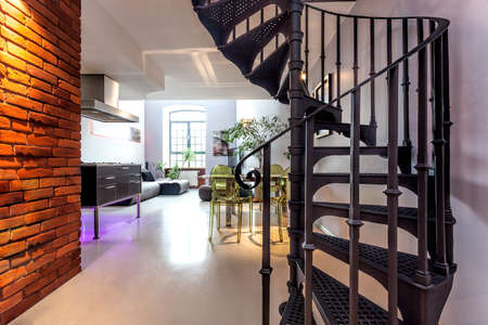 stairs interior: Spiral stairs and living room in modern loft Stock Photo