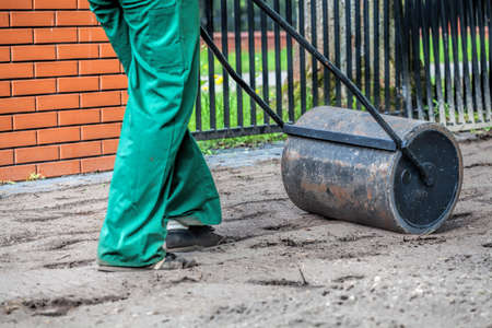 equalize: Worker equalizes a groud by roller Stock Photo
