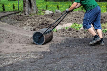 equalize: Gardener uses lawn roller to make ground plain