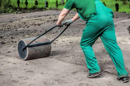 horticulturist: Pushing a lawn roller in a garden