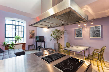 Kitchen connected with modern living room in loft apartment Stock Photo