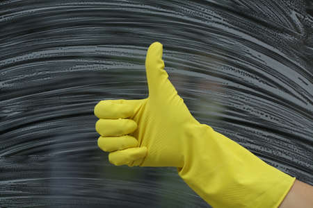window cleaner: Yellow glove for housework, before cleaning windows Stock Photo