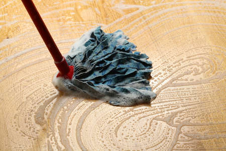 spotless: Cleaning wooden floor with mop, big housework Stock Photo