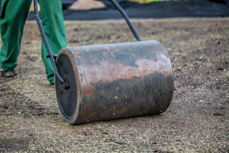 equalize: Worker with lawn roller in garden