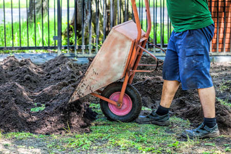 hillock: Wheelbarrow full of soil  being emptied by the gardener Stock Photo