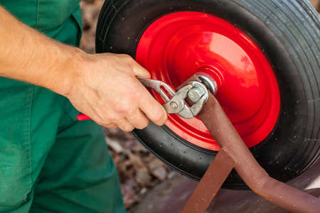 barrow: Closeup of a man reparing red wheelbarrow with pincers  Stock Photo