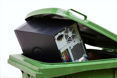 dispose: Dameged computer in a green container, isolated