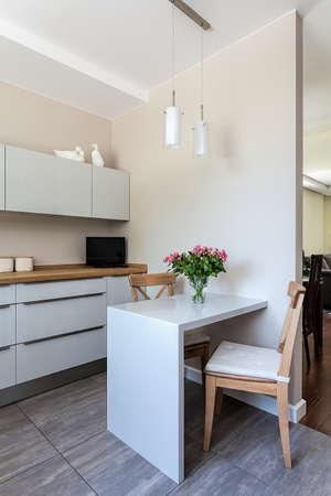 Lichte ruimte - een witte moderne keuken met eetruimte