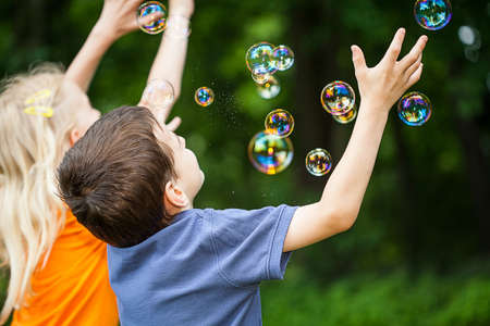 Two kids having fun blowing bubbles in the park photo