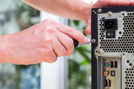 enchufe: Técnico del ordenador utiliza un destornillador para abrir hardware