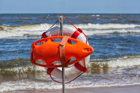 lifeboat: Lifebuoy hanging at sunny and windy seashore