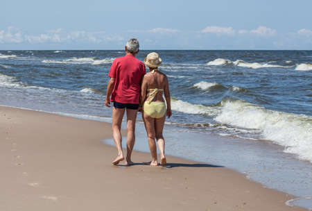 Aged couple walking at sunny seaside Фото со стока