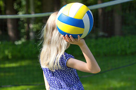 oudoors: A blonde girl playing volleyball oudoors