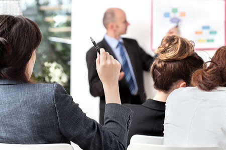 explain: Business person asking a question at a meeting Stock Photo