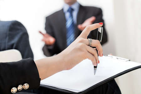 A hand holding a pen and a paper sheet at a business meeting Stock Photo - 21298993